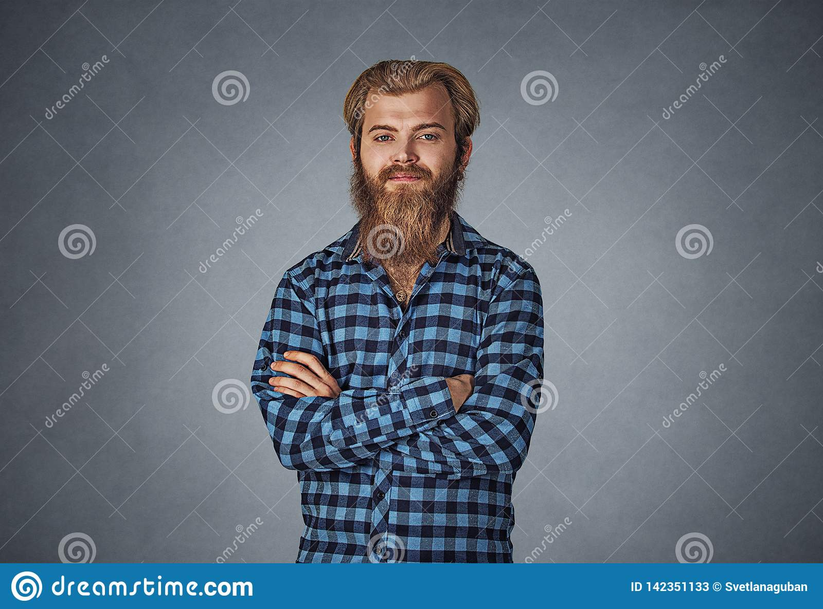 Young bearded man looking at you camera hands folded