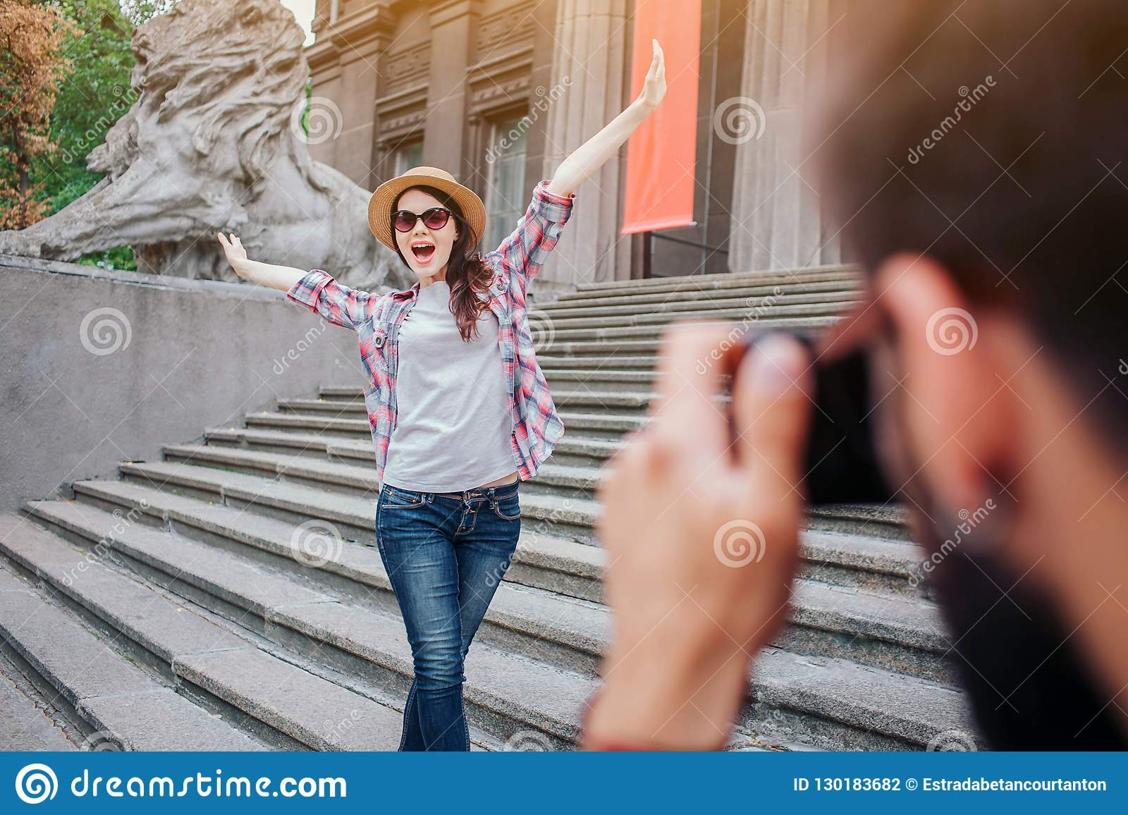 Young bearded man talking picture of happy woman. She poses on camera. Female tourist keep hands up and wears glasses