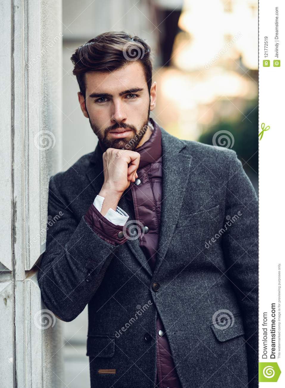 young bearded man in urban background wearing british elegant suit