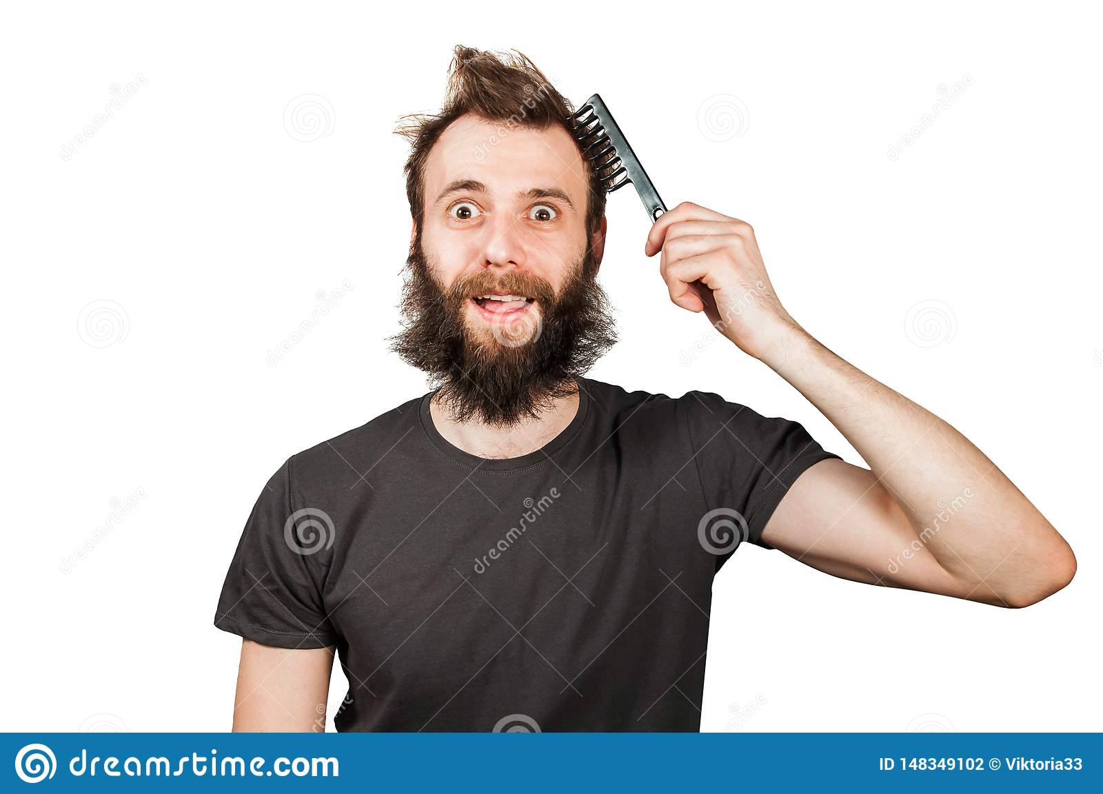Young Bearded Overgrown Man Holding Comb And Combing His