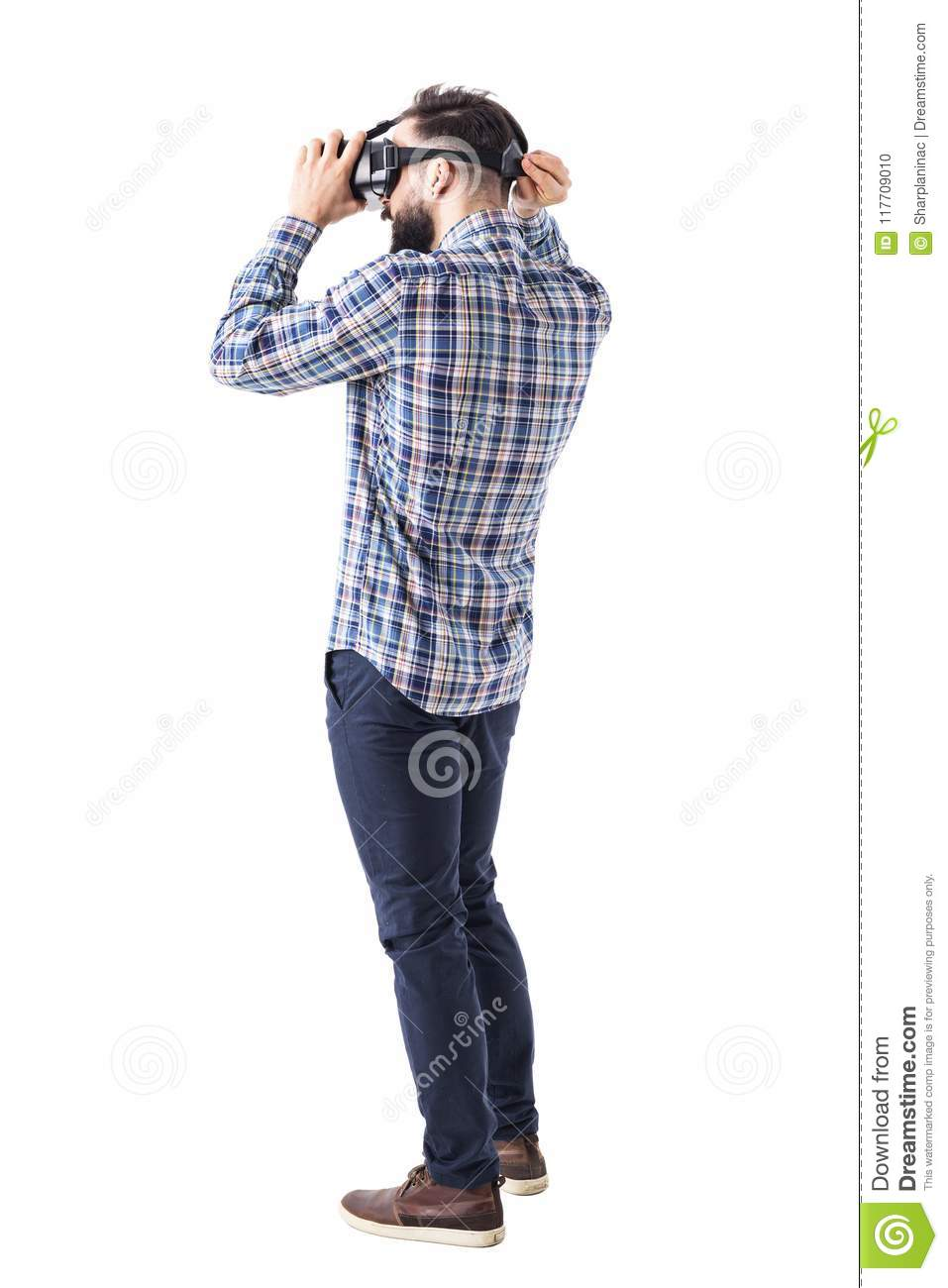 7cc3227e1531 Young bearded smart casual man putting on virtual reality glasses headset  on head. Full body isolated on white background.