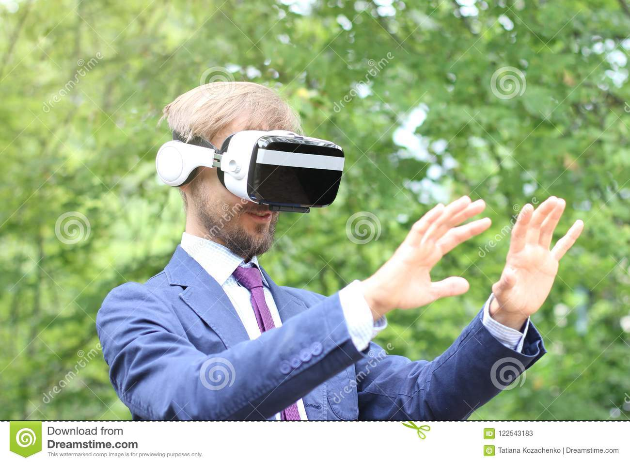 335b5790f5e7 Young bearded smiling man in suit uses virtual reality glasses outdoor.  Future technology concept.