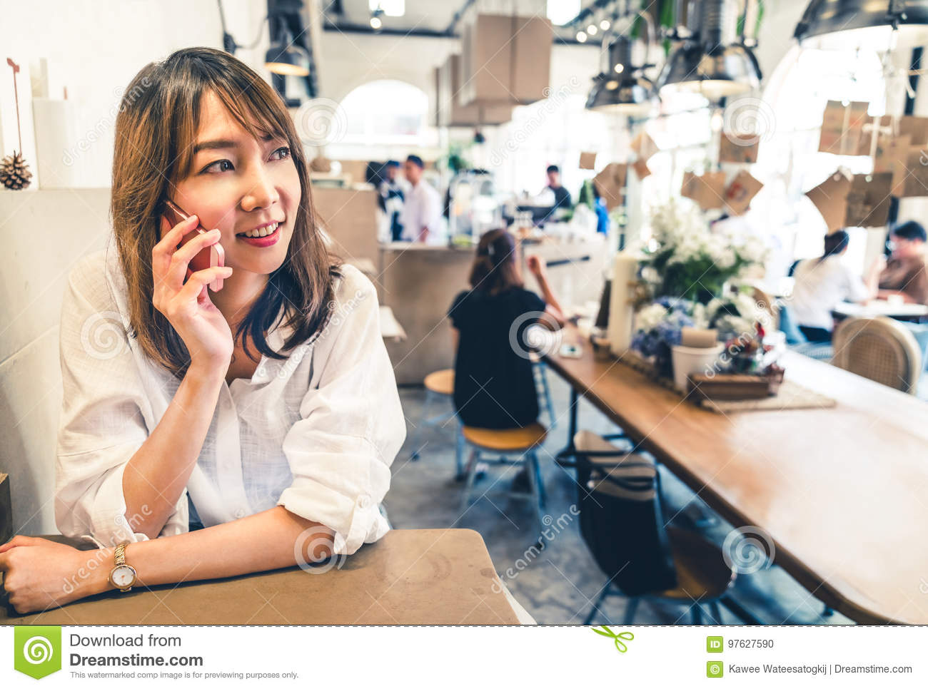 Young and beautiful Asian woman talking on mobile phone at coffee shop, communication or cafe casual lifestyle concept