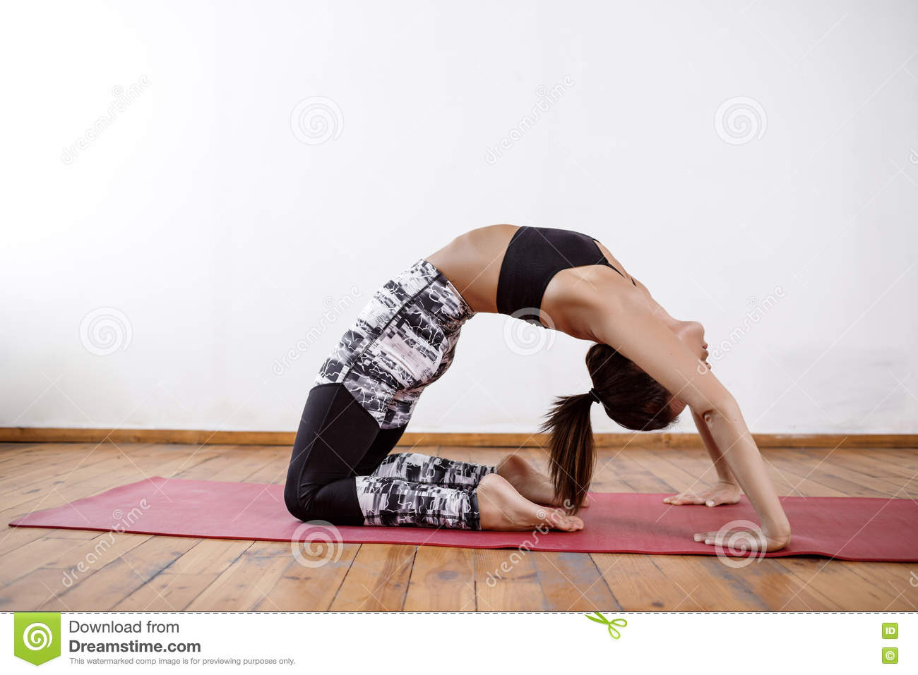 Young Beautiful Athletic Girl Practicing Indoor Yoga