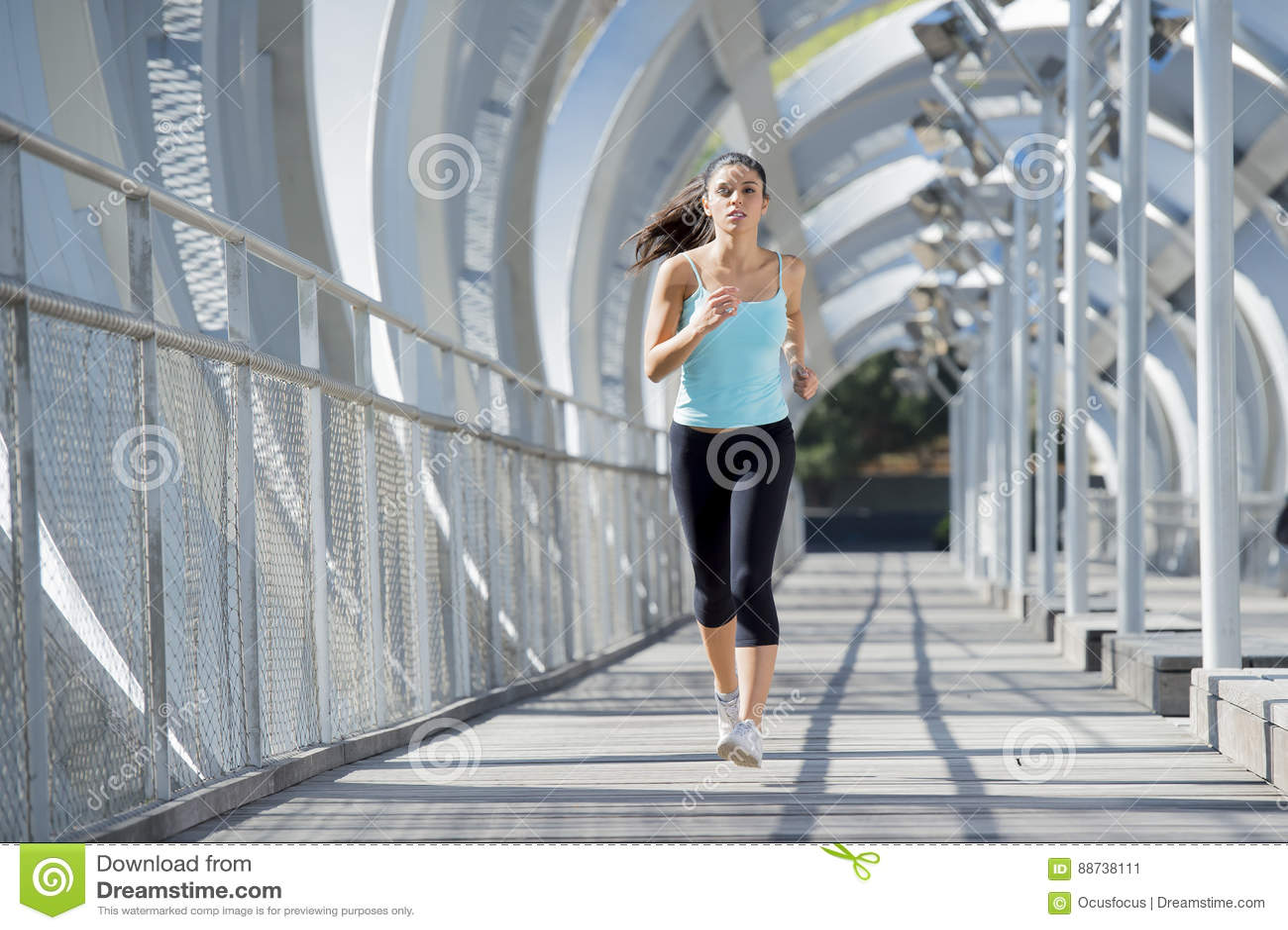 Young beautiful athletic sport woman running and jogging crossing modern metal city bridge