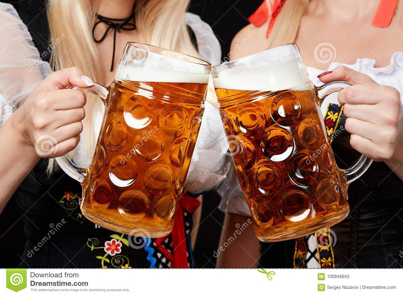 Young and beautiful bavarian girls with two beer mugs on black background