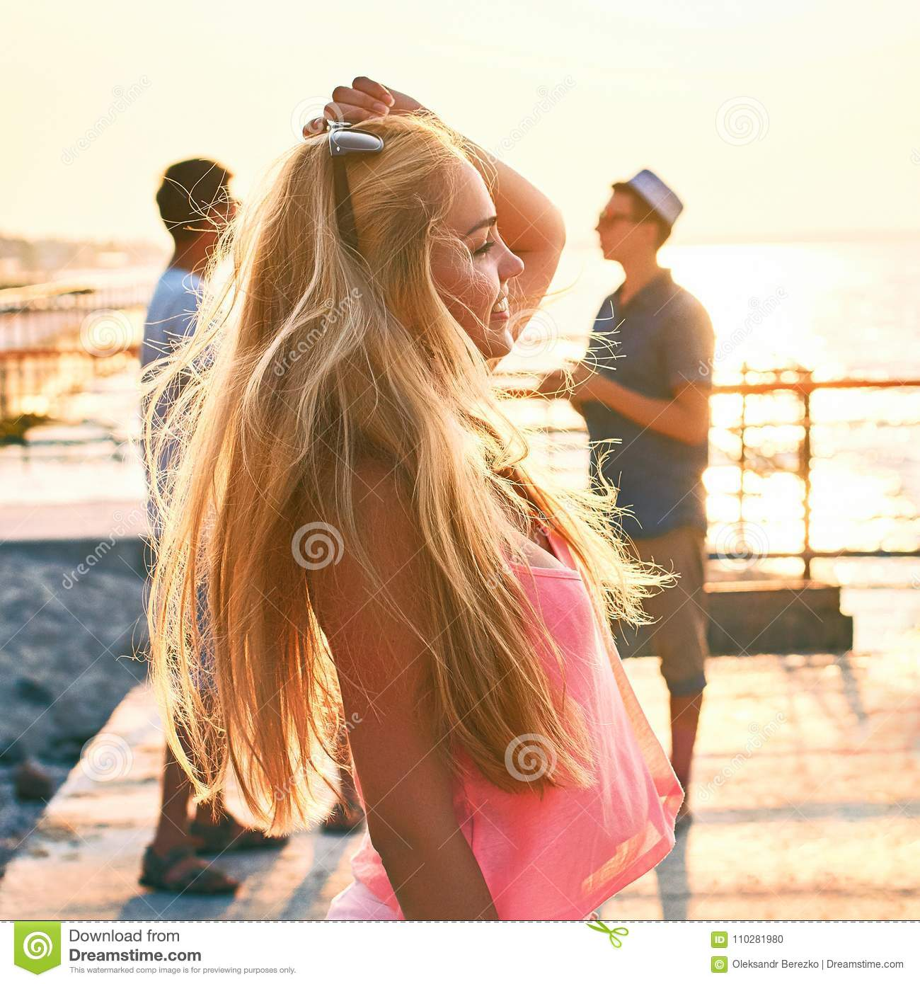 Young beautiful blonde girl in pink top having fun at the evening seaside with her friends on background