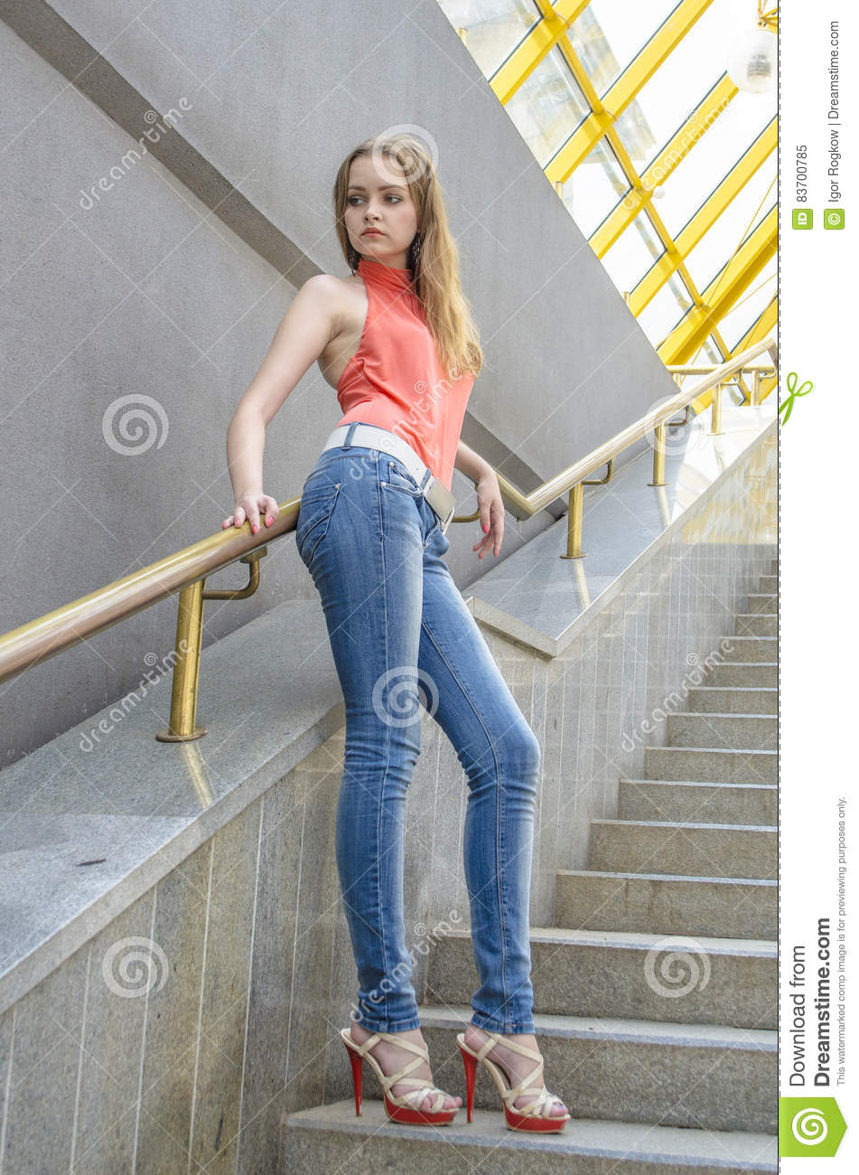 Young Beautiful Blonde Girl In A Red Summer Blouse And Jeans Posing Flexible Stock Photo