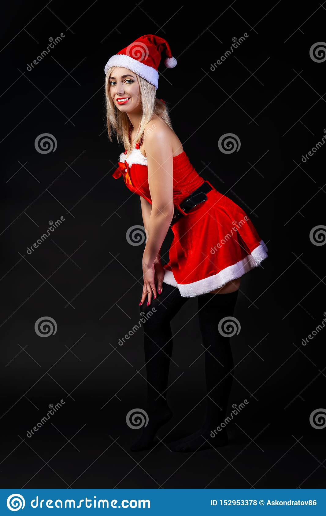 Young beautiful blonde girl in a red Snow Maiden costume or Santa Claus on a black isolated background in the Christmas and