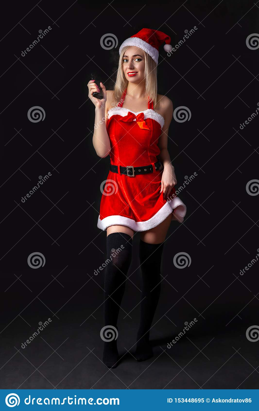 Young beautiful blonde girl in a red Snow Maiden costume or Santa Claus with vape in hand on a black isolated background in