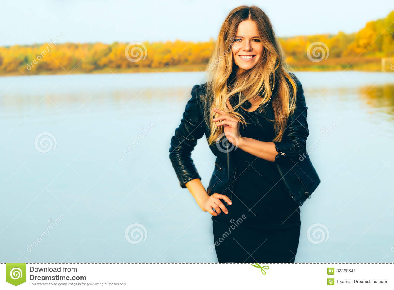 Young beautiful blonde woman in autumn park with lake in dark leather jacket smile perfect teeth during sunset.