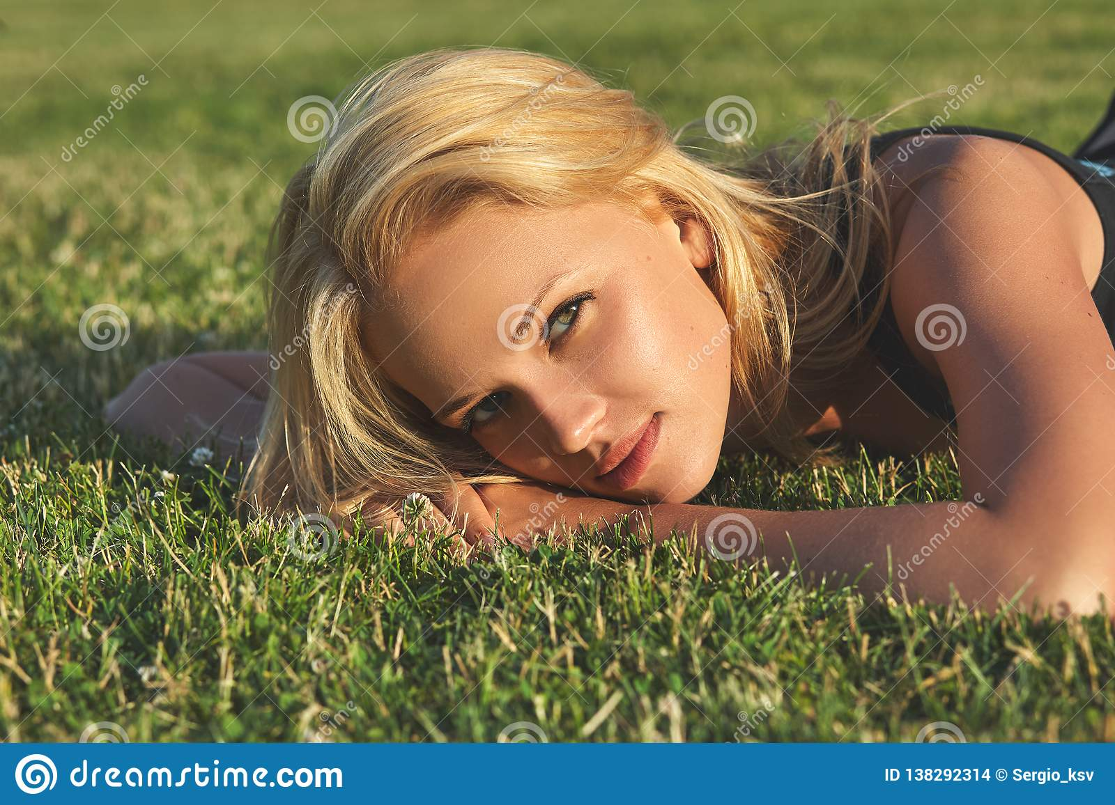 Young beautiful blonde woman relaxing on a meadow