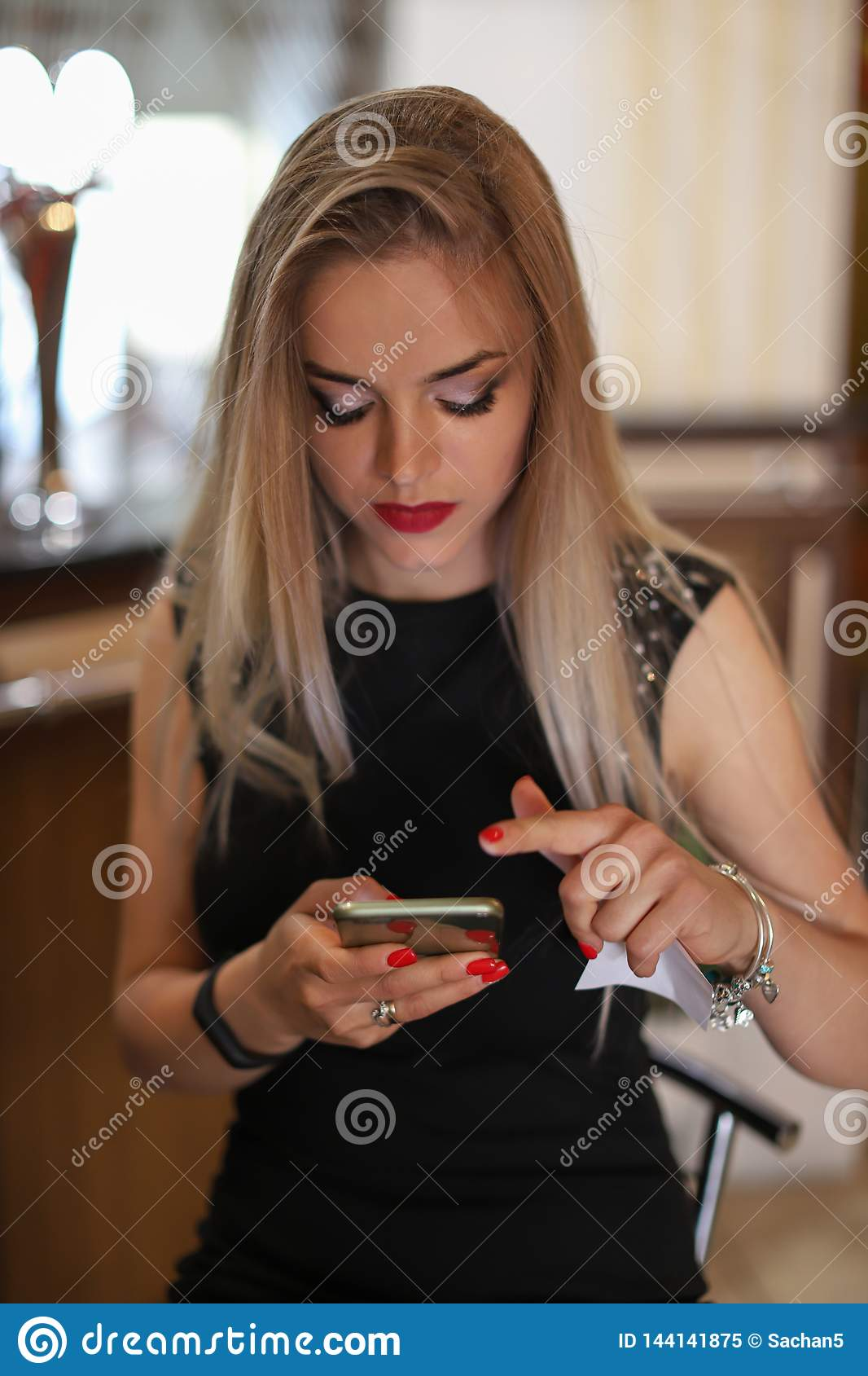 Young beautiful blonde woman writing or reading sms messages online on a smart phone in a restaurant. Young stylish girl using