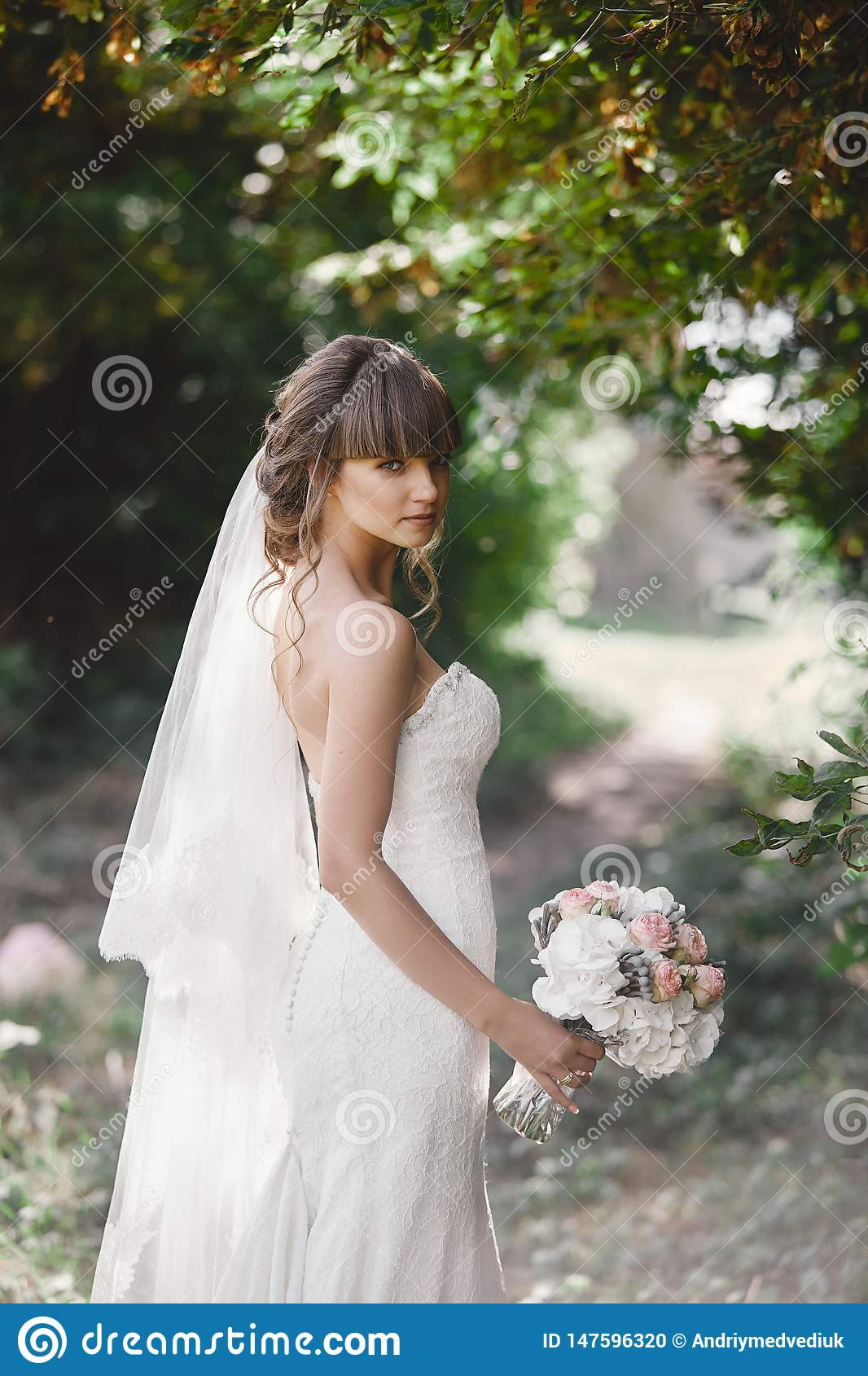 Young beautiful bride in an elegant dress is standing on the field near the forest and holding bouquet