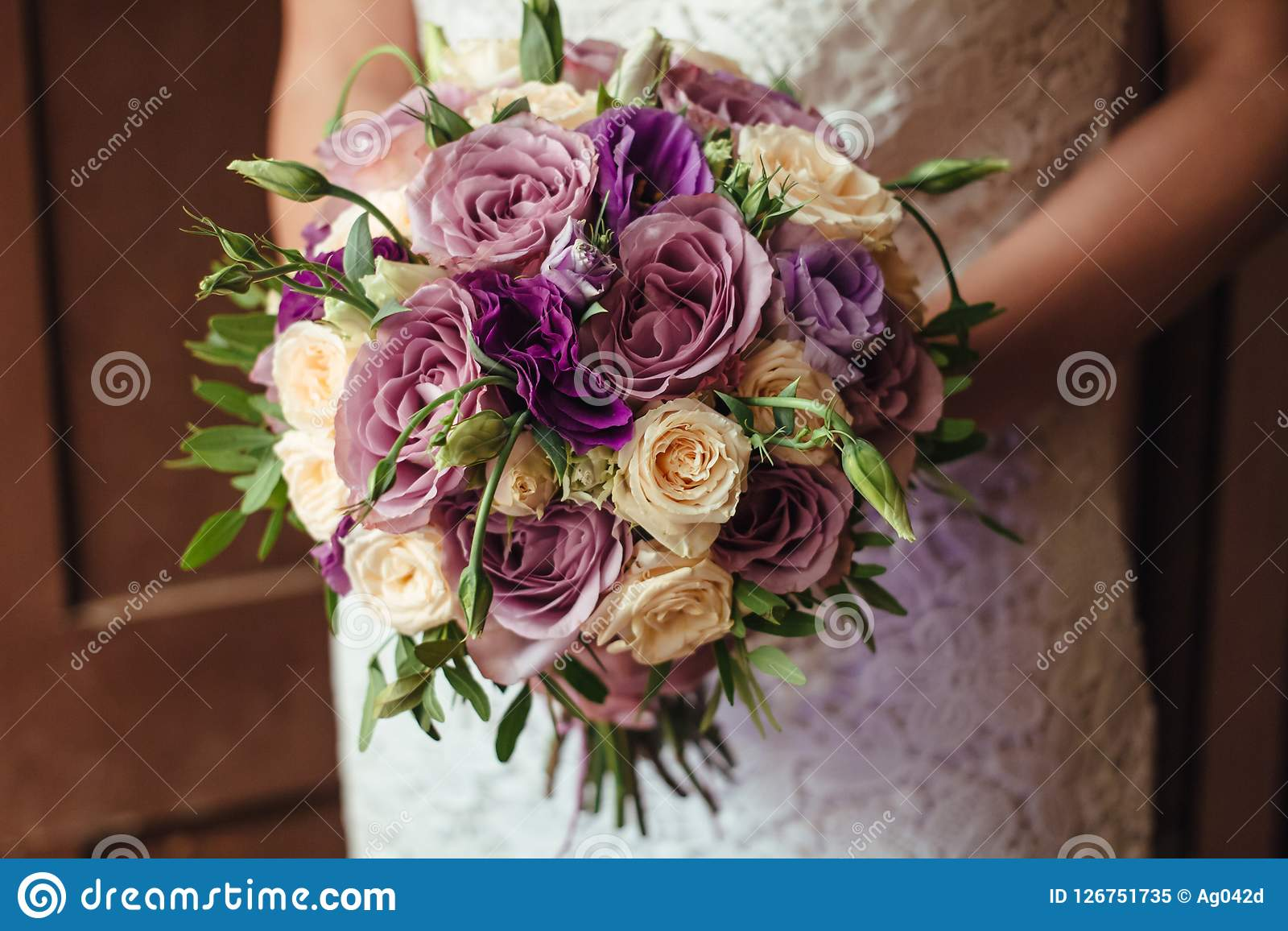 Young beautiful bride in white dress holding wedding bouquet, bouquet of bride from rose cream spray, rose bush, rose purple Memor