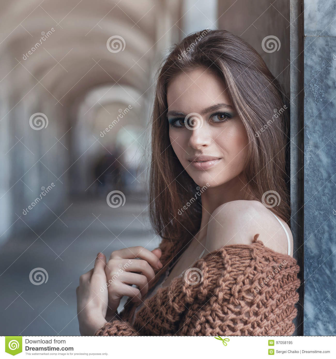 Young beautiful brunette in fashionable clothes near the wall
