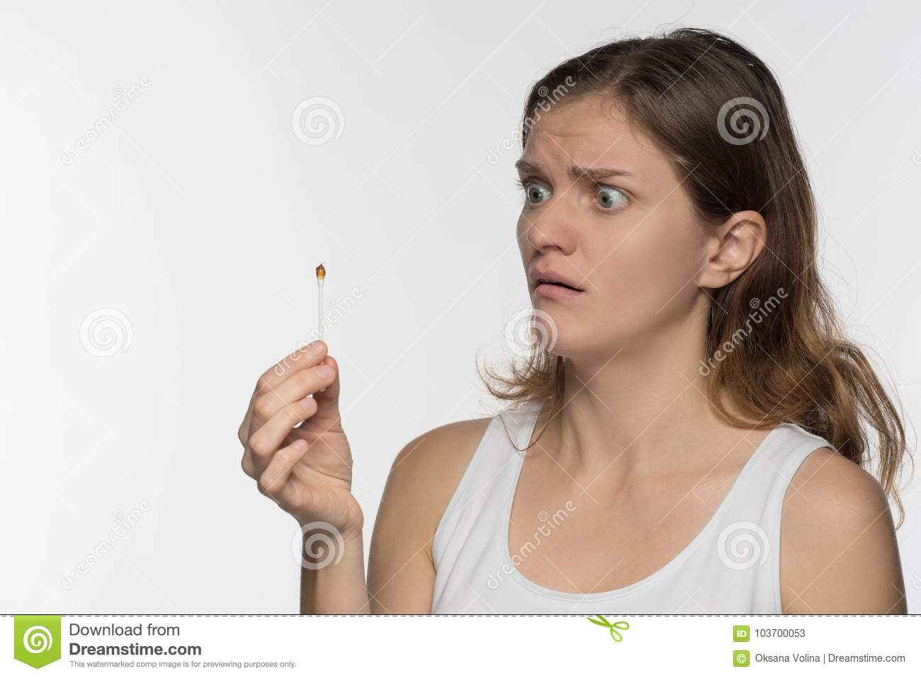 Young beautiful brunette girl cleans the ears with chopsticks wi