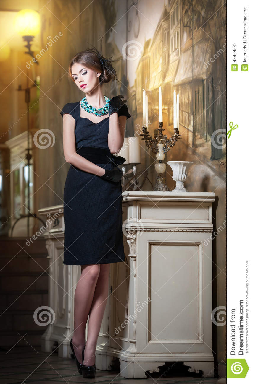 Young beautiful brunette woman in elegant black dress standing near a candlestick and wallpaper. Sensual romantic lady