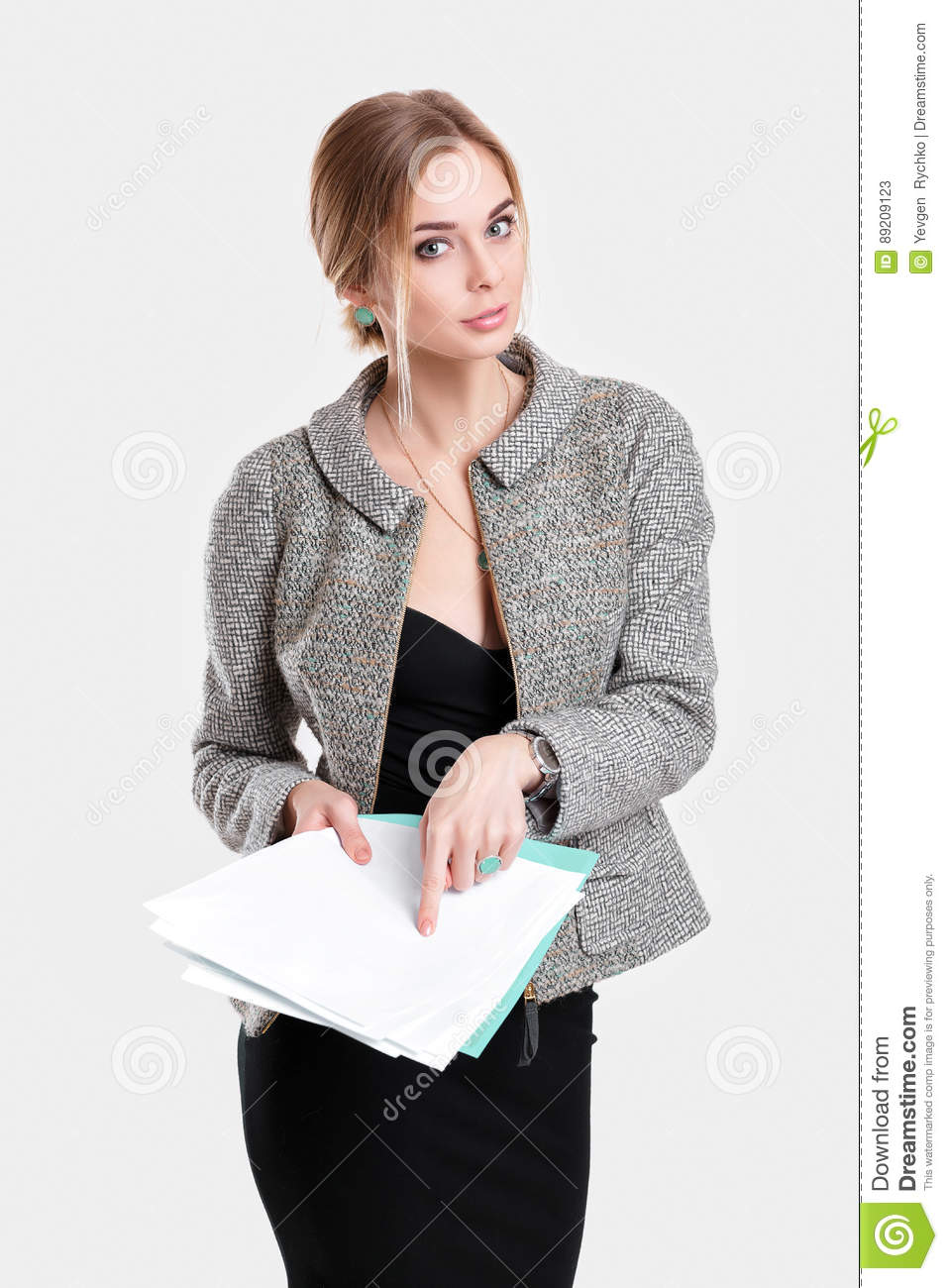 Young beautiful business woman in black dress, jacket holding folder of papers and smiling on gray background