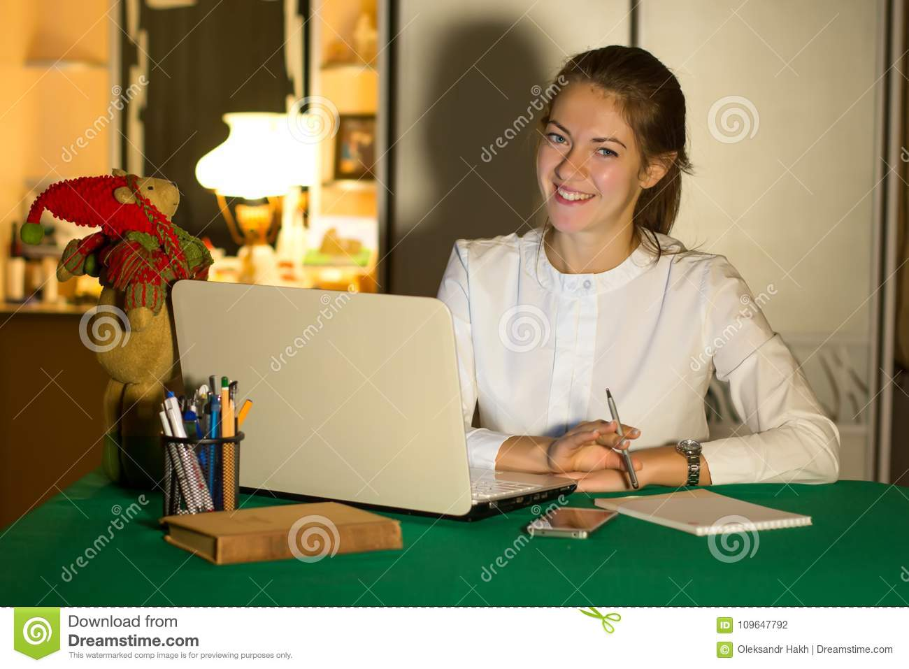 Young beautiful business woman running a home at laptop in a cozy environment. Freelancer works in the house.