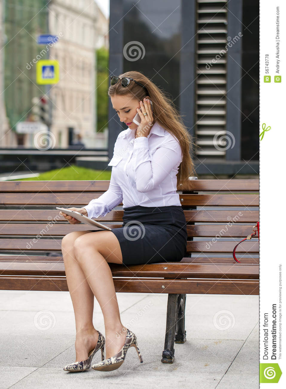 Young beautiful business woman sitting on a bench in the sunny c