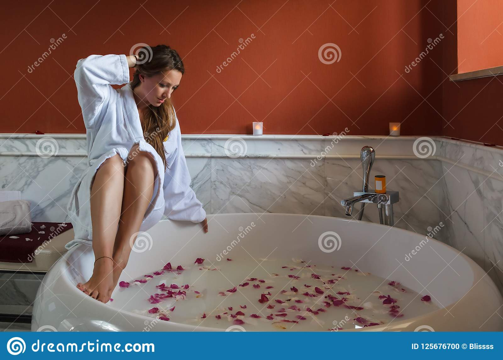 Young beautiful Caucasian brunette woman in white bathrobe is about to have spa bath with rose petals. Wellness and recreation tou