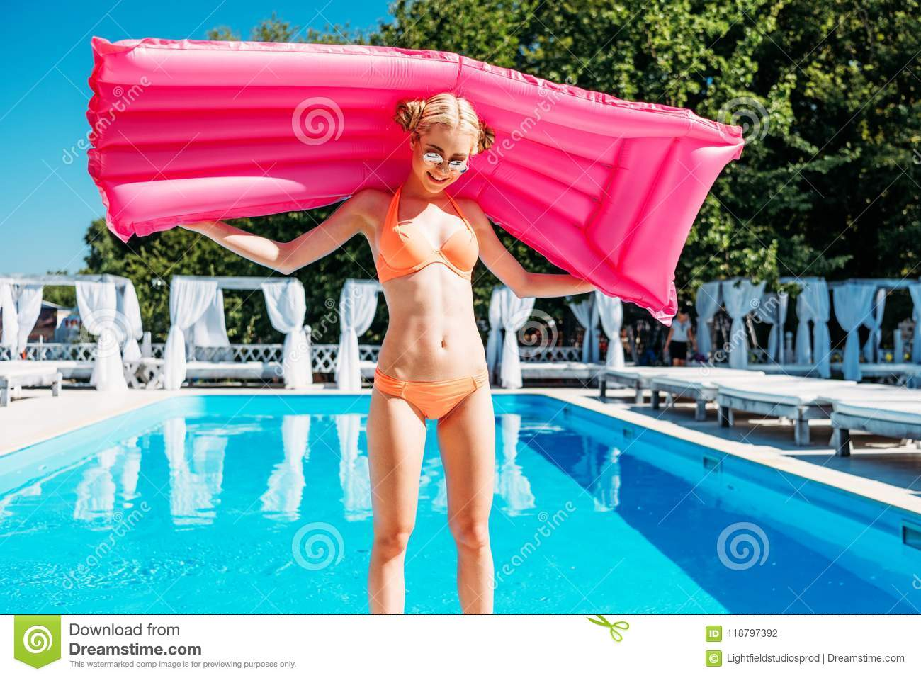 Young beautiful caucasian woman posing with inflatable mattress at poolside