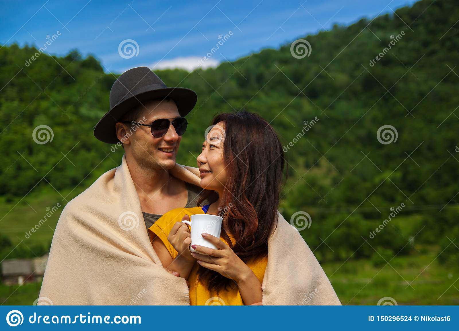 Young beautiful couple in the forest enjoy nature and drink tea.