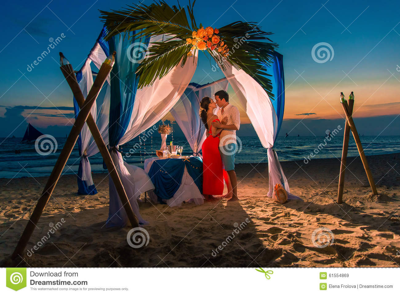 Young beautiful couple have a romantic dinner at sunset