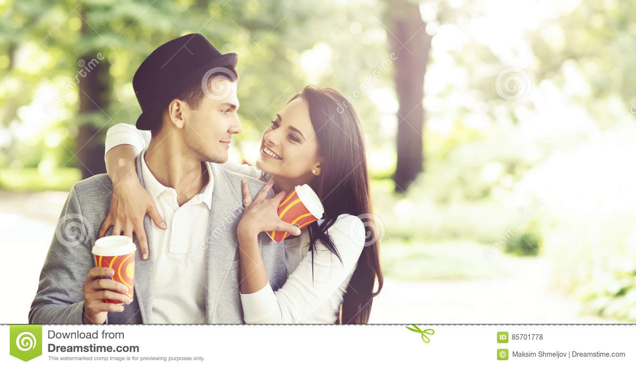 Young beautiful couple of hipsters: hugging in the park.
