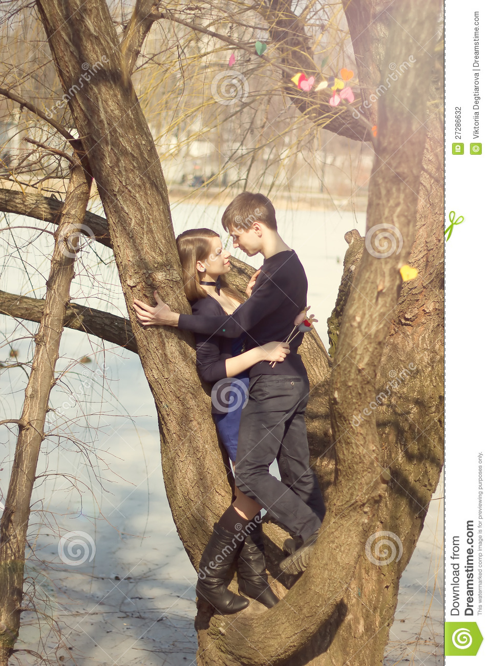 young beautiful couple hugging against the tree stock photo