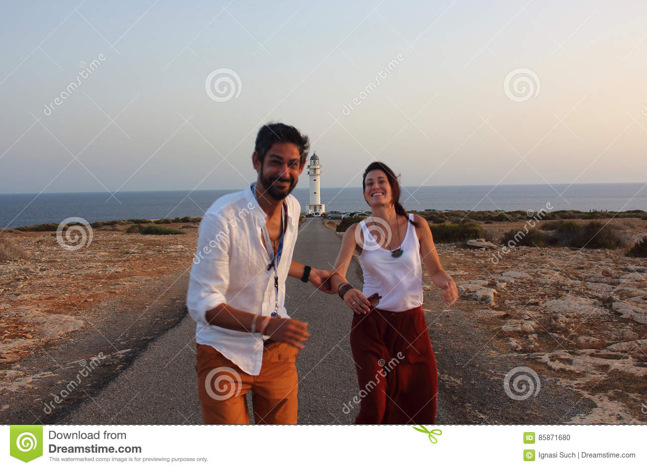 Young beautiful couple`s portrait with Cap de Barberia`s lighthouse on soft background, Formentera, Balearic Islands, Spain