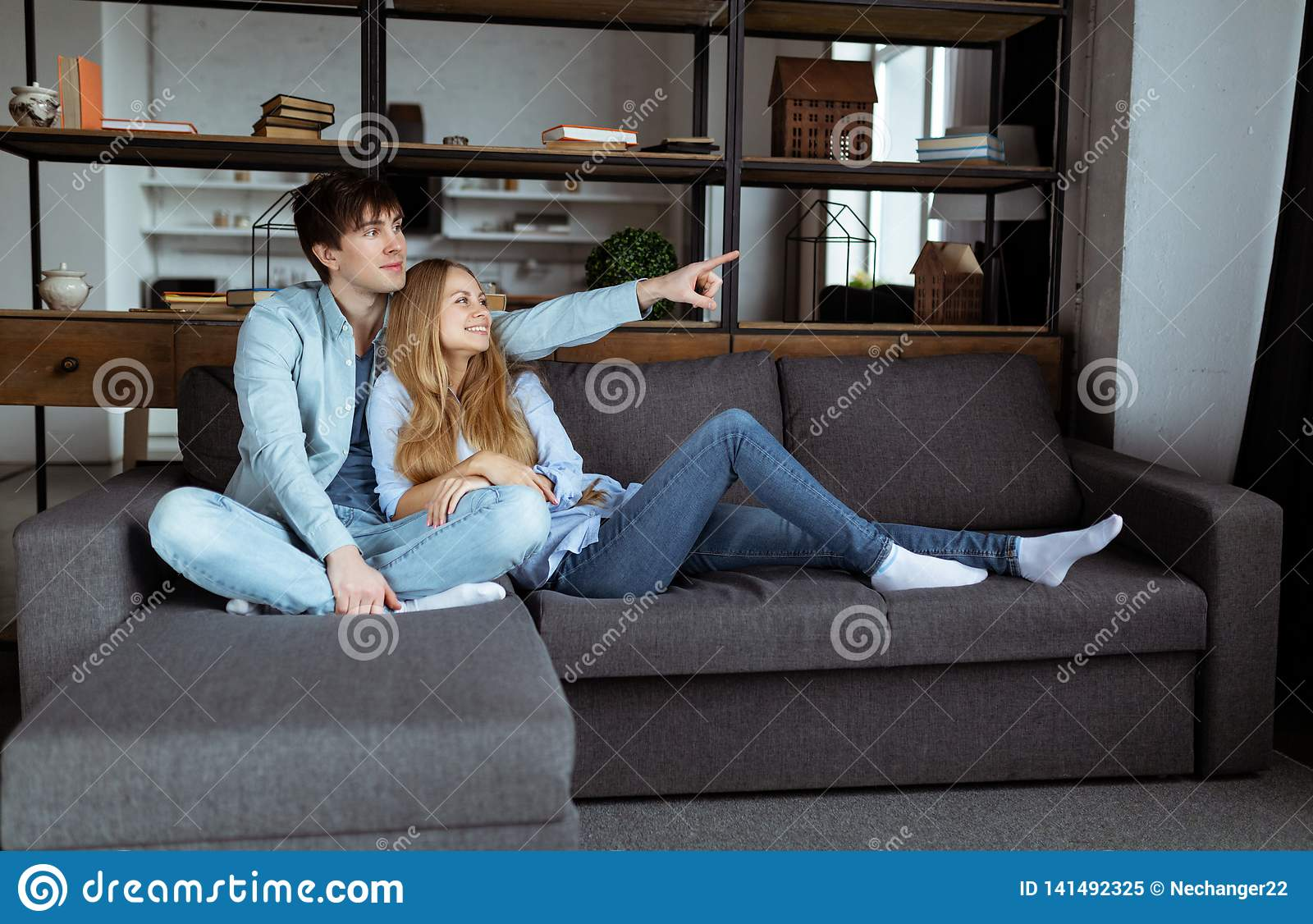 Young beautiful couple sitting on the sofa watching TV together