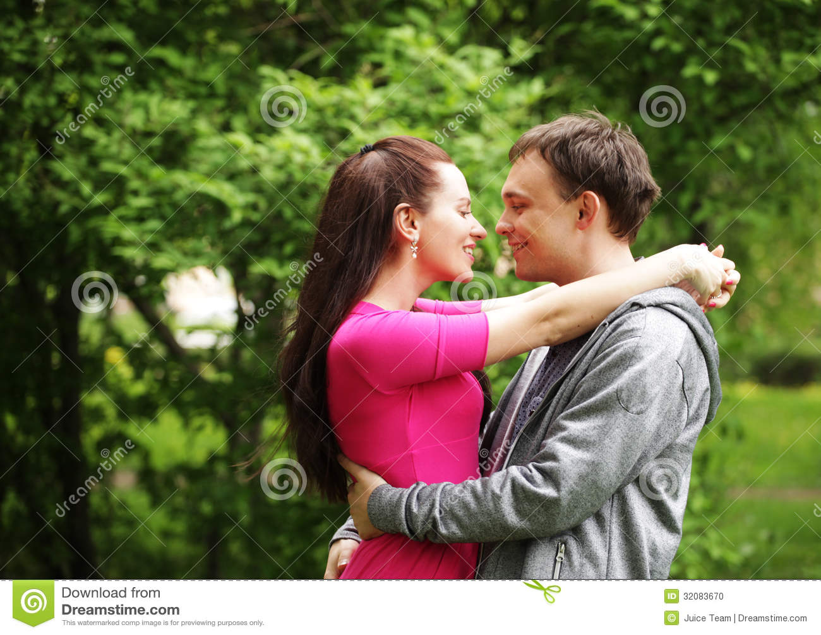 Young beautiful couple in a sweet cheek kiss