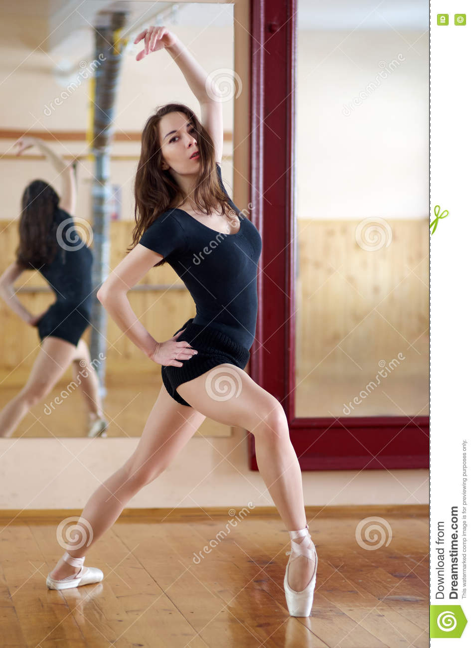 Young beautiful dancer posing in fitness center on a studio mirror background