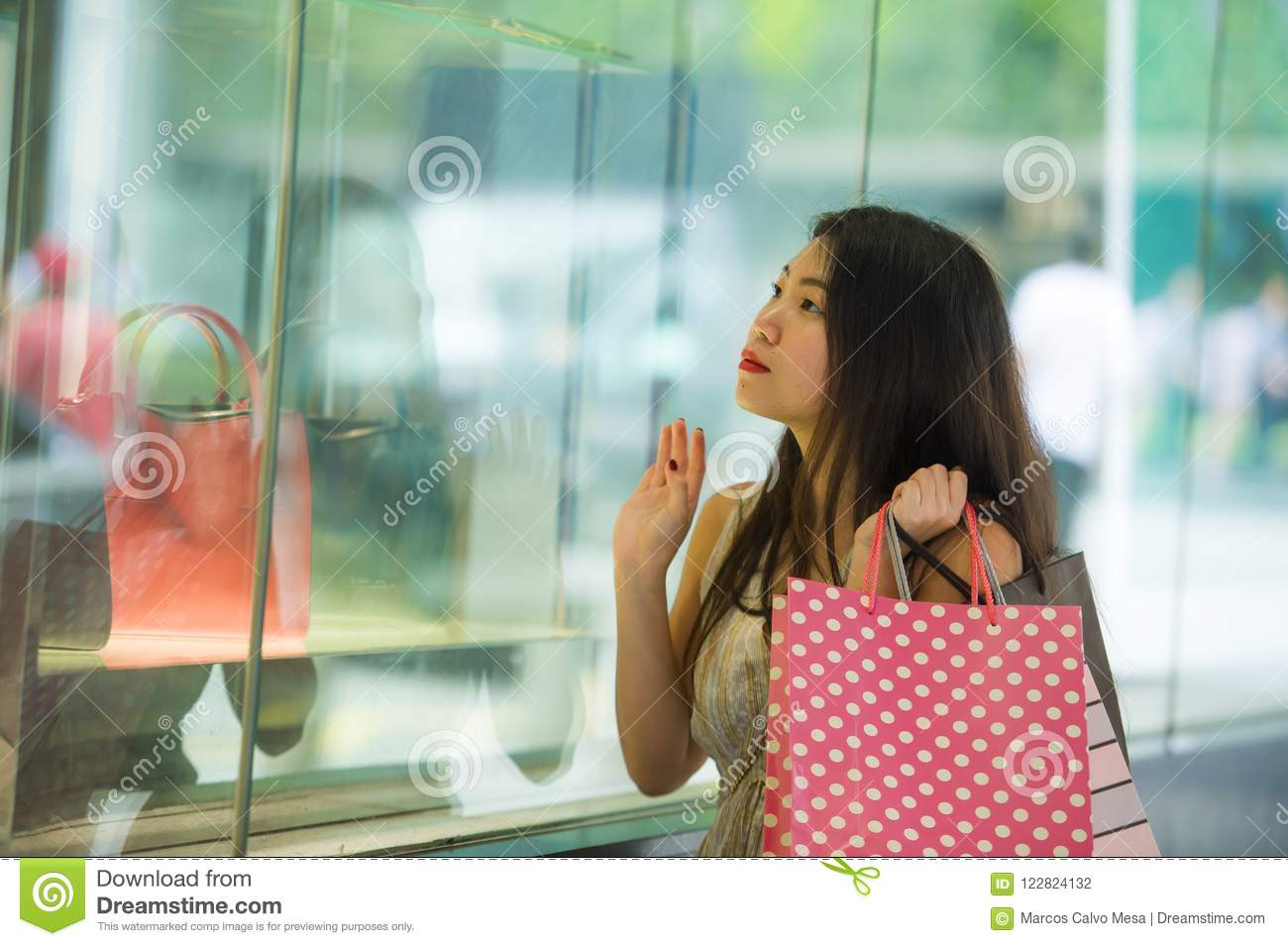 f2eebbbb4c8 Young beautiful and elegant Asian Korean woman holding shopping bags after buying  walking on street looking at clothing window store with sweet face ...