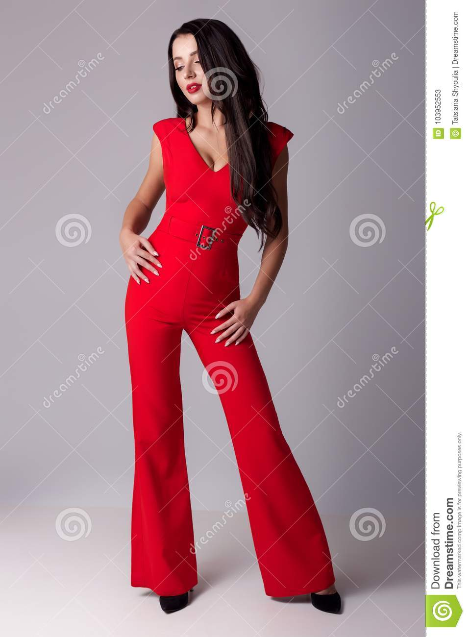 Young beautiful fashionable woman with long dark hair a slender figure in the studio