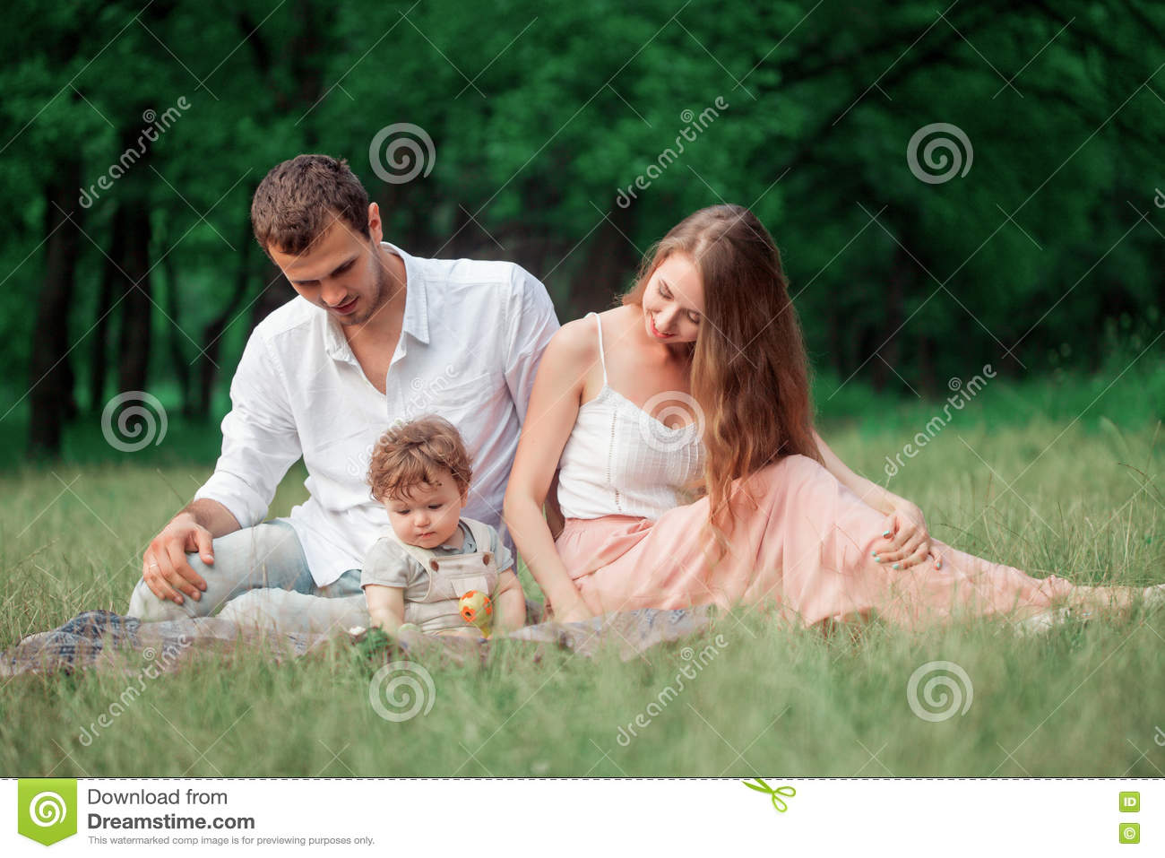 Young beautiful father, mother and little toddler son against green trees