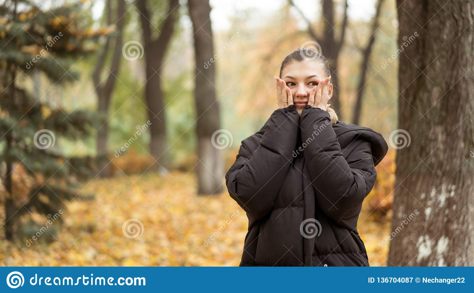 0a518dfe5ae Young beautiful girl in the autumn park in black jacket standing near a  tree and cover her face with hands. Trees and leaves on background. Autumn  concept
