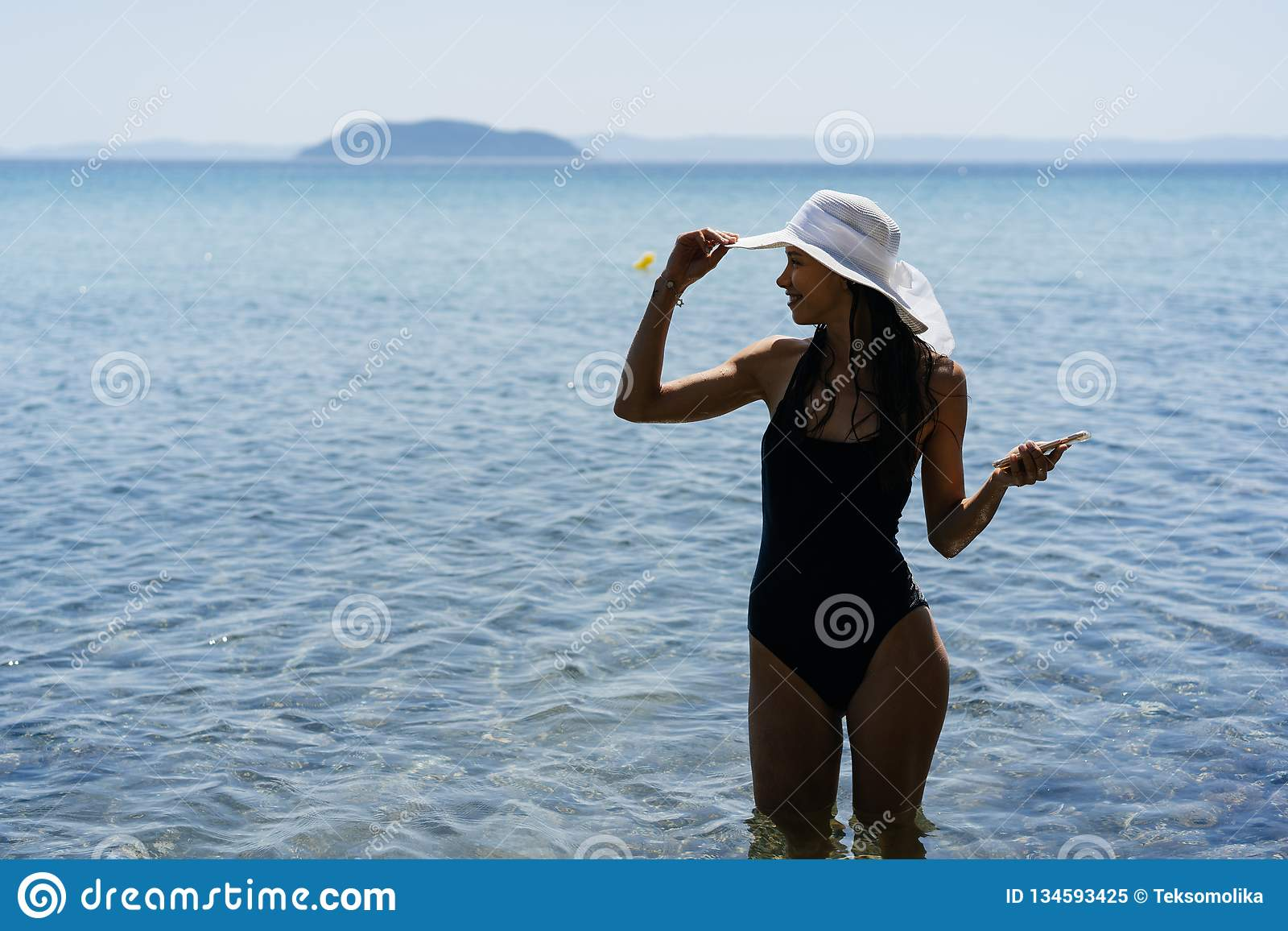 002f1dcd67bb0 Young beautiful girl in a bathing suit and a striped hat is standing  against the blue sea. Girl posing on camera