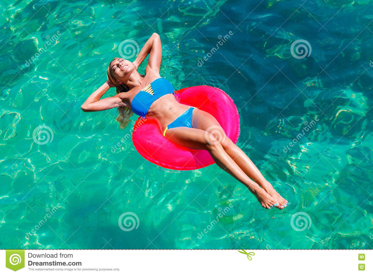 Young beautiful girl in bikini swims in a tropical sea on a rubber ring. Summer vacation concept.