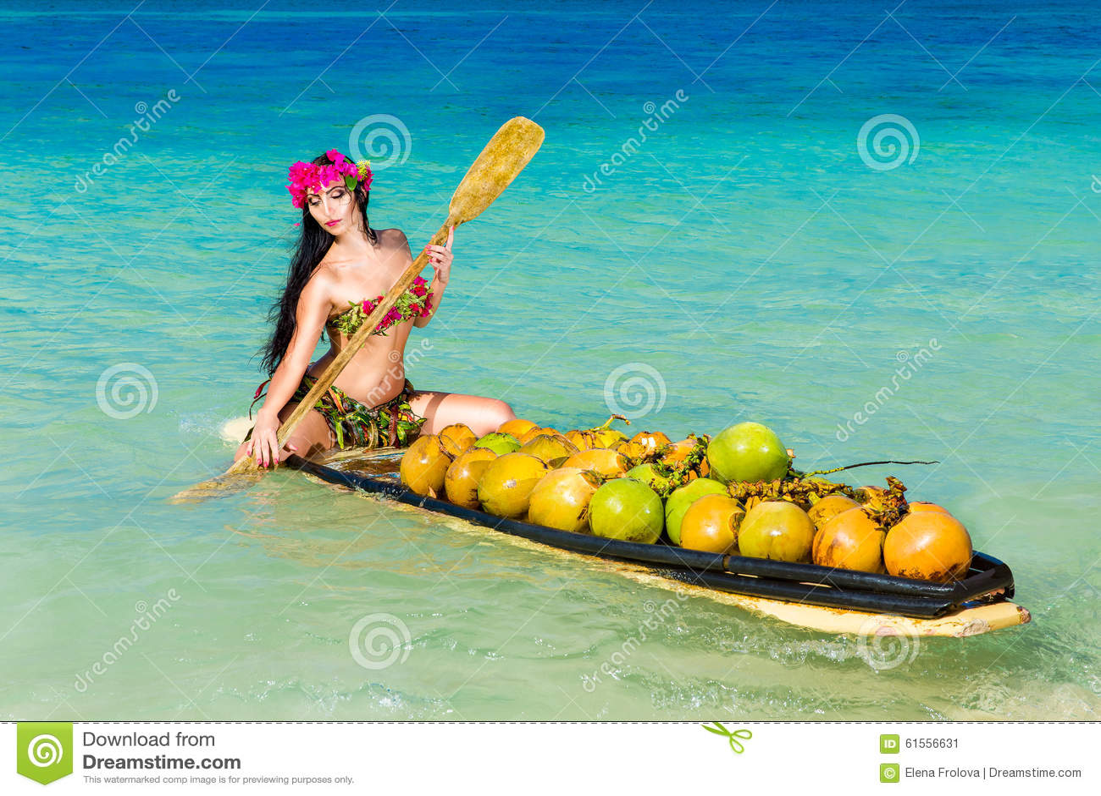 Young beautiful girl in a bikini with tropical flowers sitting i