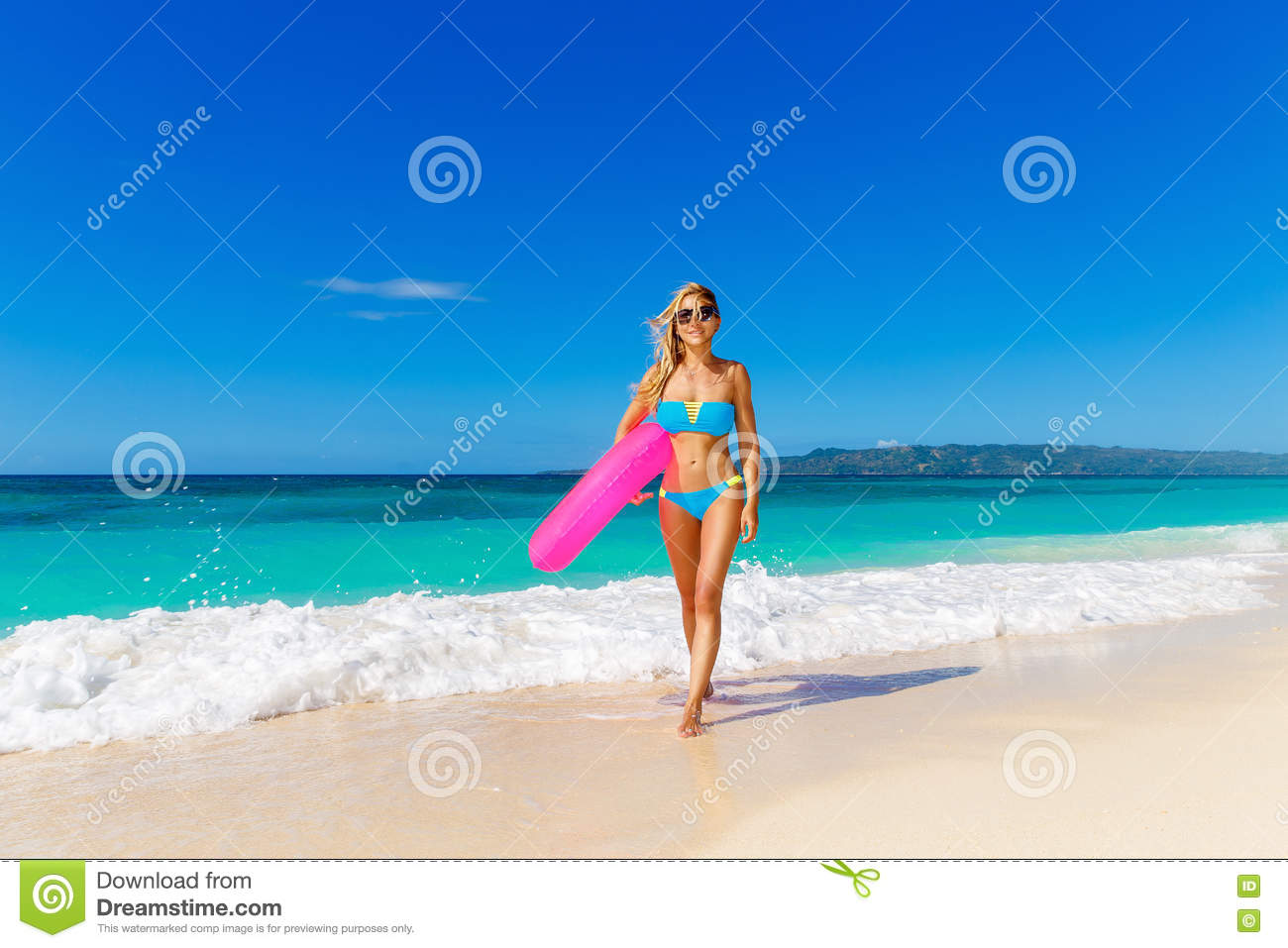 Young beautiful girl in blue bikini having fun on a tropical beach with rubber ring for swimming. Blue sea and sky in