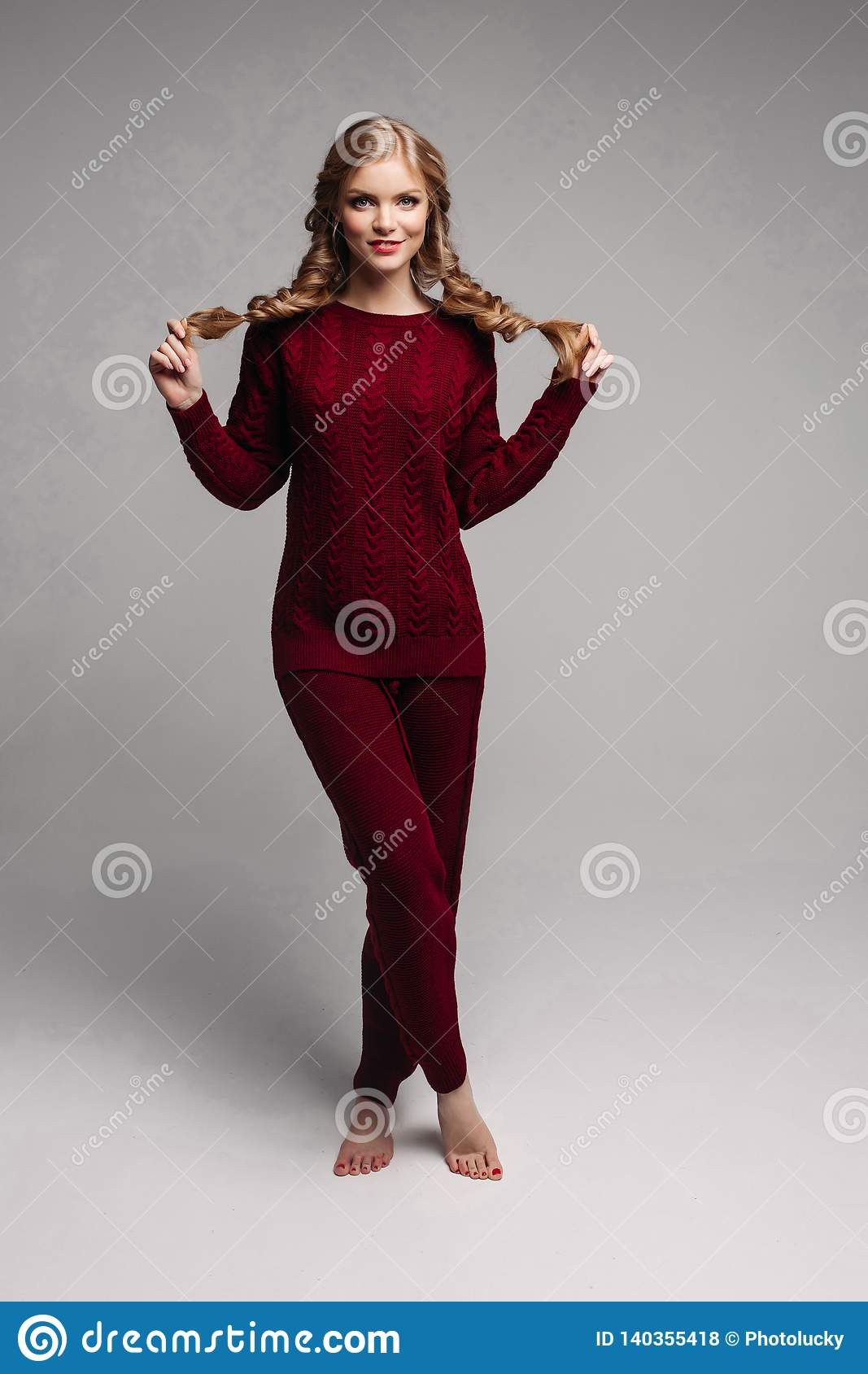 6f7b3b1e99 Young beautiful girl in bordo sweater and pants posing at camera. Amazing blonde  lady holding her braids and standing on toes with pedicure.