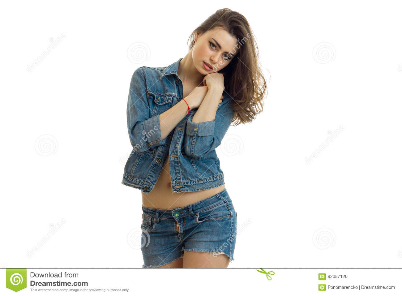 Young beautiful girl in denim shorts and a jacket keeps your hands near your face and looks straight