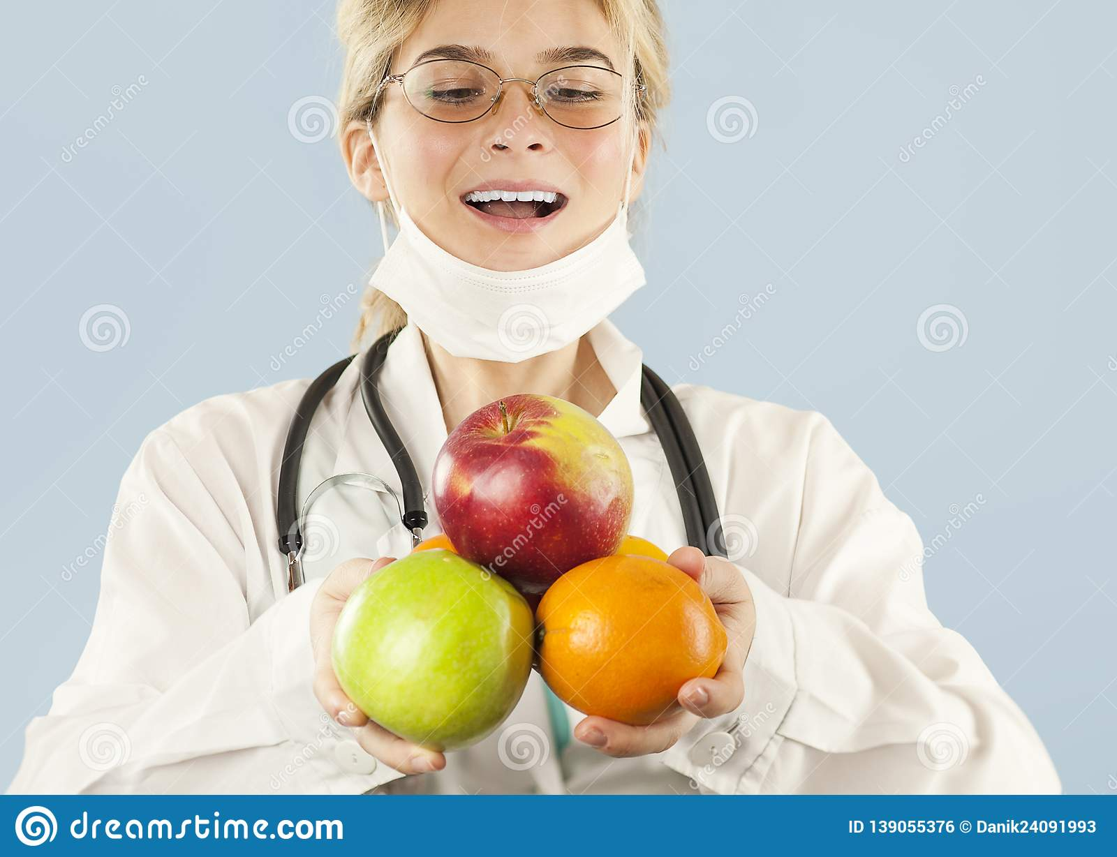 Beautiful girl doctor nutritionist with fruit in hand on blue isolated background. Healthy eating concept