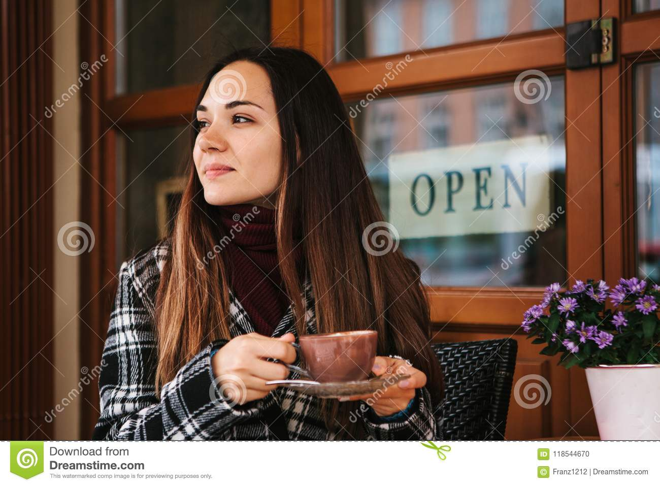 Young Beautiful Girl Drinks Coffee Or Hot Chocolate In A Street Cafe