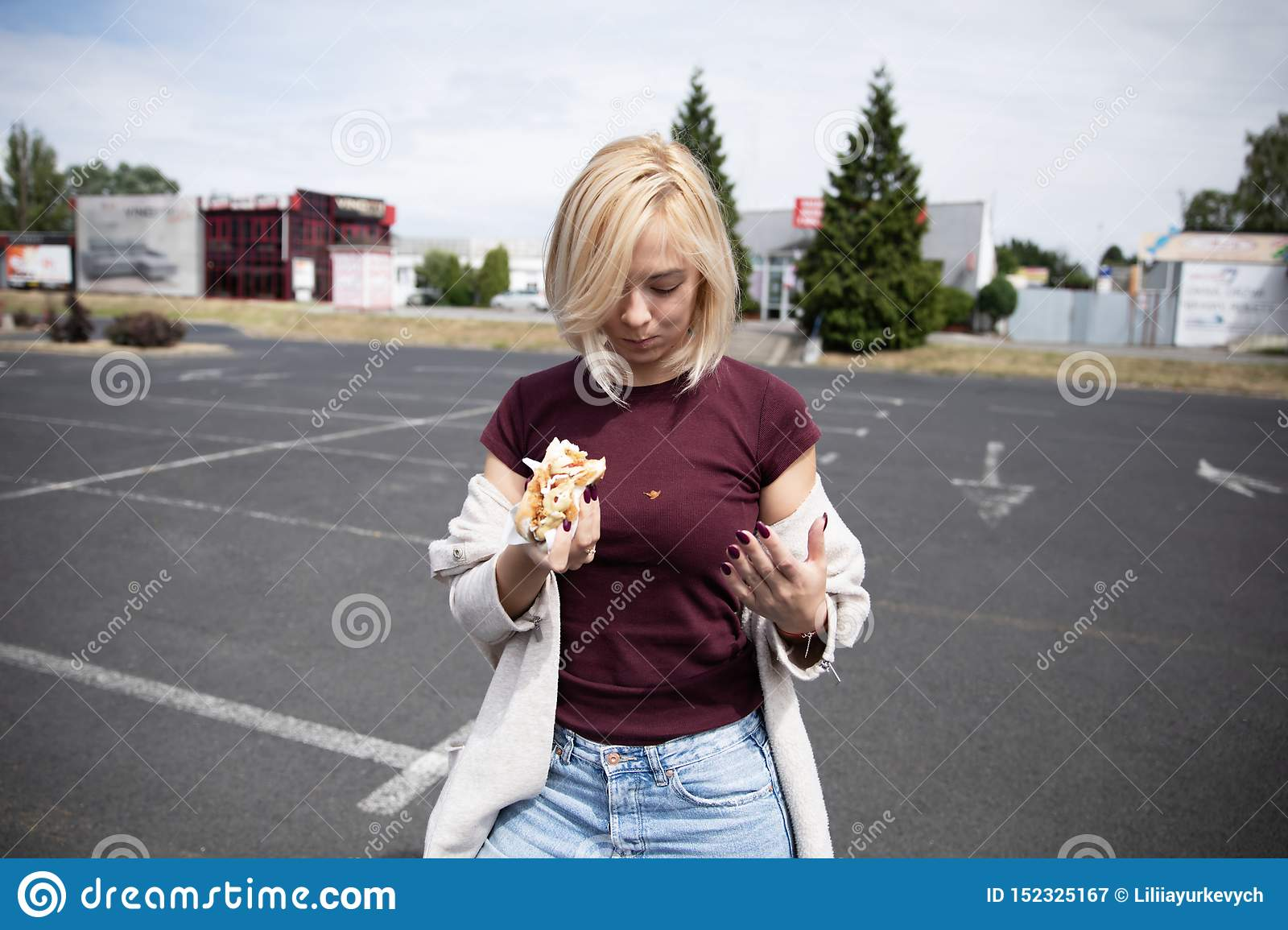 A young woman holds a bitten hot dog