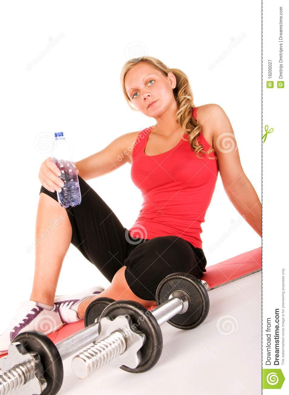 Young beautiful girl at the gym drinking water