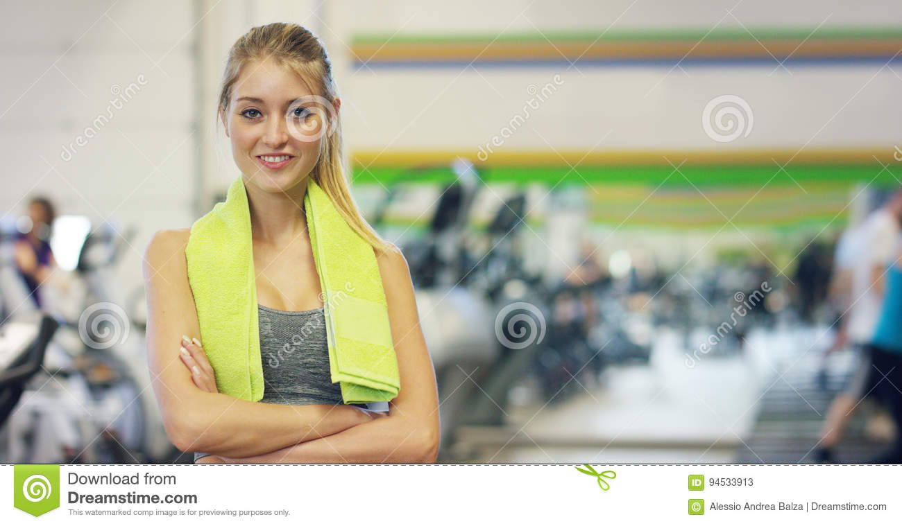 Young beautiful girl in the gym, stands smiling with a towel on her shoulder after the coaching and relaxed. Concept: to love spor